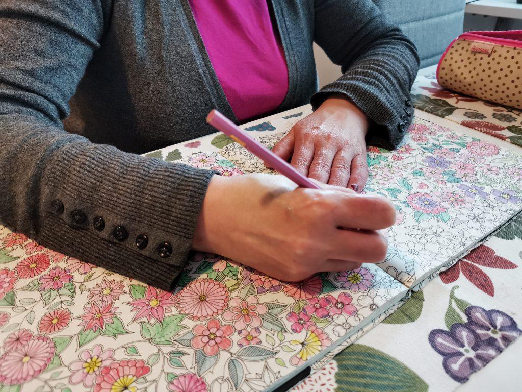 Tuetun asumisen asukas Elisabet värittää värityskirjaa. Lähikuva kirjasta.