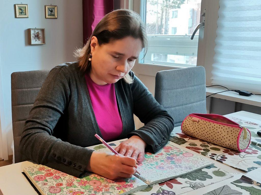 Tuetun asumisen asukas Elisabet värittää värityskirjaa.