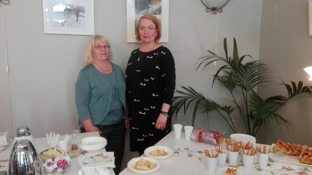 Lilinkotisäätiön vapaaehtoinen Kaarina ja avoimen toiminnan toiminnanohjaaja Laura poseeravat avoimen toiminnan syyskauden avajaisissa kahvipöydän luona.