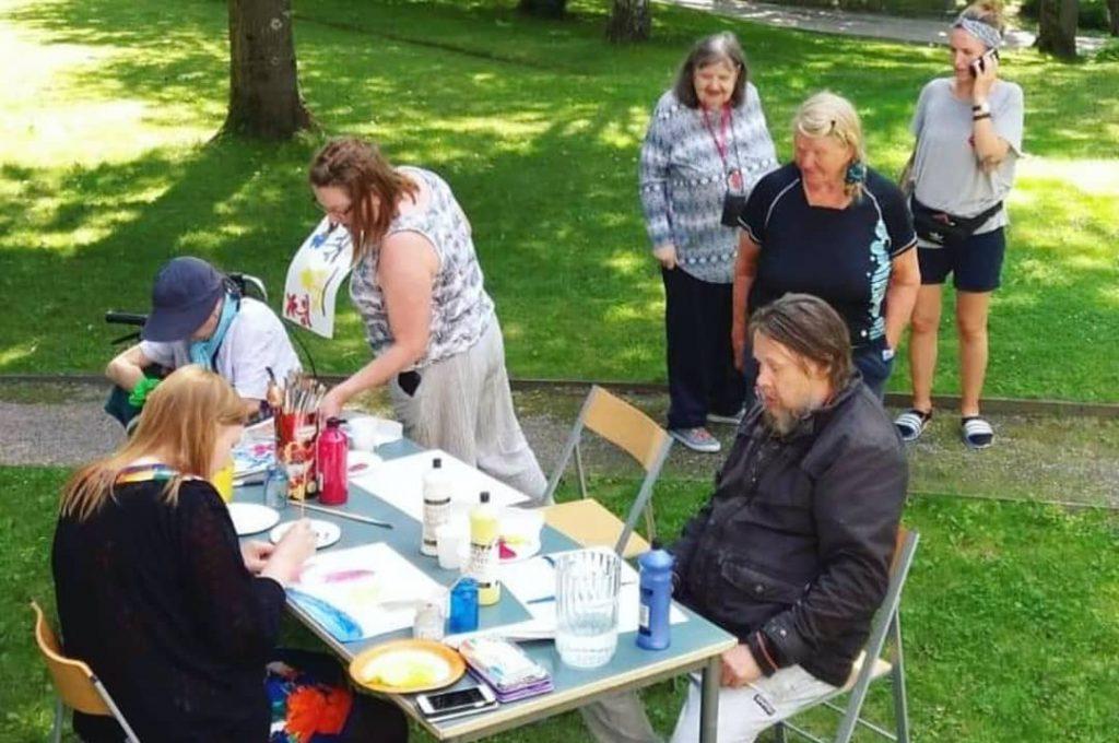 Kesäkahvilassa järjestettiin monipuolista ohjattua toimintaa. Kuvassa maalataan pöydän ääressä.